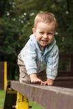 Muchacho joven feliz que se arrastra en la escala Foto de archivo libre de regalías