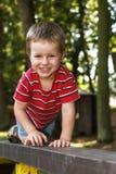 Muchacho joven feliz que se arrastra en la escalera Imagenes de archivo