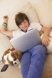 Muchacho joven feliz que se relaja en casa Foto de archivo
