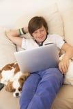 Muchacho joven feliz que se relaja en casa Fotografía de archivo