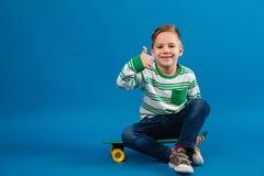 Muchacho joven feliz que se sienta en el monopatín y que muestra el pulgar para arriba Foto de archivo libre de regalías