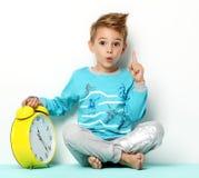 Muchacho joven feliz que se sienta en el suéter azul que piensa y que mira para arriba Imagenes de archivo