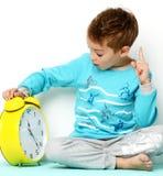 Muchacho joven feliz que se sienta en el suéter azul que piensa y que mira para arriba Imagen de archivo libre de regalías