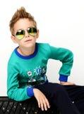Muchacho joven feliz que se sienta en suéter verde en gafas de sol tipo aviador Fotografía de archivo libre de regalías