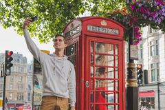 Muchacho joven feliz que toma un selfie delante de una caja del teléfono en Londond imagenes de archivo