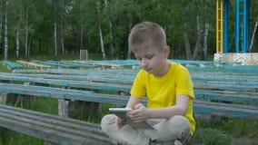 Muchacho joven feliz que usa la tableta almacen de video