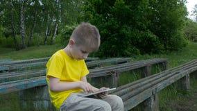 Muchacho joven feliz que usa la tableta almacen de metraje de vídeo