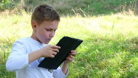Muchacho joven feliz que usa la tableta metrajes