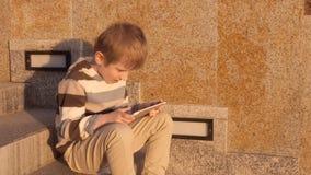 Muchacho joven feliz que usa la tableta en el parque almacen de video