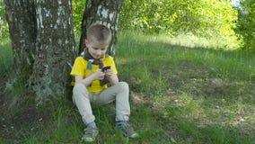 Muchacho joven feliz que usa smartphone en el parque almacen de video