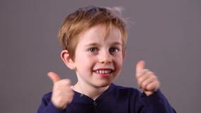 Muchacho joven fresco del preschoool que muestra su entusiasmo con los pulgares para arriba almacen de video
