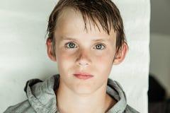 Muchacho joven hermoso con el pelo mojado en una sudadera con capucha Fotografía de archivo