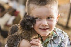 Muchacho joven hermoso con el pollo de la demostración Fotografía de archivo