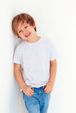 Muchacho joven hermoso, niño que presenta cerca de la pared blanca fotos de archivo libres de regalías