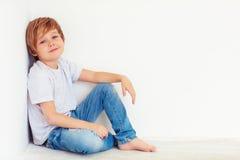 Muchacho joven hermoso, niño que presenta cerca de la pared blanca imágenes de archivo libres de regalías