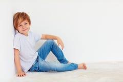 Muchacho joven hermoso, niño que se sienta cerca de la pared blanca foto de archivo libre de regalías