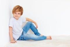 Muchacho joven hermoso, niño que se sienta cerca de la pared blanca fotos de archivo libres de regalías