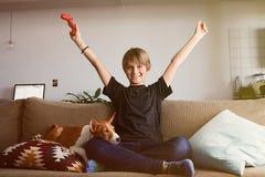 Muchacho joven hermoso que celebra su victoria en la consola del videojuego asentada en un sofá con el perrito del perro del base imágenes de archivo libres de regalías