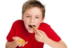 Muchacho joven hermoso que come las fritadas Foto de archivo