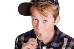 Muchacho joven hermoso que goza de una piruleta Fotografía de archivo libre de regalías