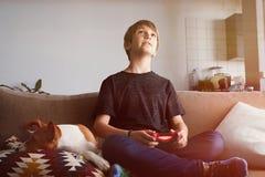 Muchacho joven hermoso que juega la consola del videojuego asentada en un sofá con el perrito del perro del basenji que duerme ce imagen de archivo libre de regalías