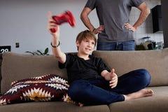 Muchacho joven hermoso que juega la consola del videojuego asentada en un sofá mientras que su situación del padre cercana en sal foto de archivo libre de regalías