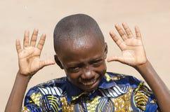 Muchacho joven hermoso que muestra las manos que ríen al aire libre Fotos de archivo