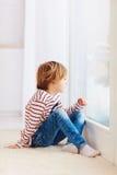 Muchacho joven hermoso que se sienta en la alfombra cerca de la ventana en casa foto de archivo