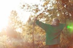 Muchacho joven, lanzamiento con el arco hecho a mano y flecha en la blanco en la puesta del sol, aire libre del verano fotos de archivo
