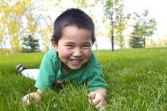 Muchacho joven lindo con la gran sonrisa que pone en hierba imagen de archivo libre de regalías