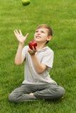 Muchacho joven lindo con las manzanas en hierba verde Foto de archivo
