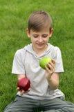Muchacho joven lindo con las manzanas en hierba verde Fotografía de archivo