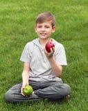 Muchacho joven lindo con las manzanas en hierba verde Foto de archivo libre de regalías