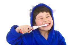 Muchacho joven lindo con los dientes que aplican con brocha de la gran sonrisa foto de archivo