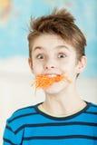 Muchacho joven lindo con una boca rellena con la zanahoria Imagen de archivo libre de regalías