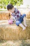 Muchacho joven lindo de la raza mixta que pone monedas en la hucha Imagen de archivo libre de regalías