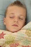 Muchacho joven lindo dormido bajo paz de la manta del copo de nieve Fotos de archivo