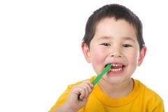 Muchacho joven lindo que aplica sus dientes con brocha aislados imagenes de archivo