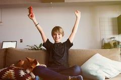 Muchacho joven lindo que celebra su victoria en la consola del videojuego asentada en un sofá con el perrito del perro del basenj fotografía de archivo libre de regalías