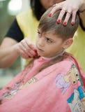 Muchacho joven lindo que consigue corte de pelo Imagen de archivo libre de regalías