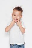 Muchacho joven lindo que hace una cara divertida contra un fondo blanco Foto de archivo libre de regalías