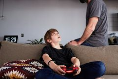 Muchacho joven lindo que juega la consola del videojuego asentada en un sofá mientras que su situación del padre cercana en sala  imagen de archivo