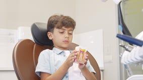 Muchacho joven lindo que sonríe a la cámara, llevando a cabo el modelo del diente almacen de video