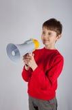 Muchacho joven lindo que sostiene el altavoz en sus manos Imagen de archivo