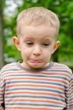 Muchacho joven lindo que tira de una expresión divertida Fotos de archivo libres de regalías