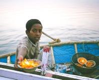 Muchacho joven no identificado que vende las placas con las flores y las pequeñas velas de diyas para la ceremonia de Ganga Aarti Imagen de archivo libre de regalías