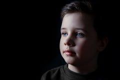 Muchacho joven pensativo en un retrato oscuro Fotos de archivo