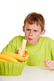 Muchacho joven poco impresionado que come un plátano fresco Fotos de archivo