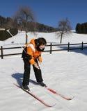 Muchacho joven por la primera vez con esquí de fondo Foto de archivo libre de regalías