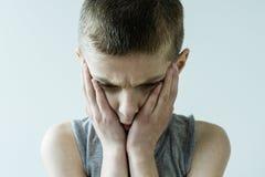 Muchacho joven preocupado que sostiene la cara en manos Imagen de archivo